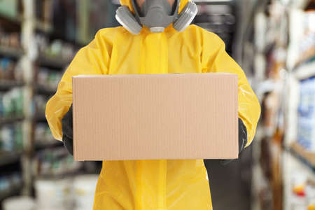 Man wearing chemical protective suit with cardboard box in store, closeup. Wholesale market