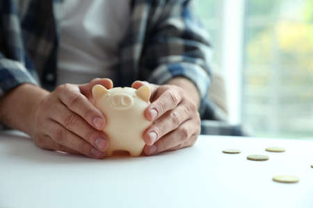 Man with piggy bank at white table against blurred background, closeup