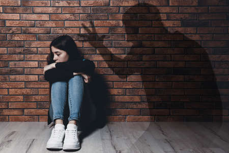 Child abuse. Father yelling at his daughter. Shadow of man on brick wall