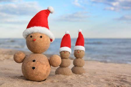 Snowmen made of sand with Santa hats on beach near sea. Christmas vacation