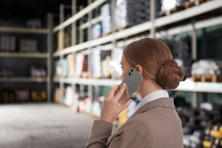 Wholesale and logistics concept. Manager talking on phone in warehouse