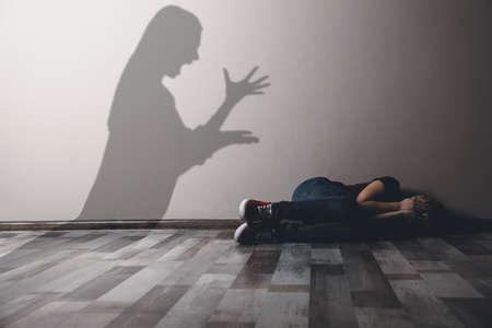 Child abuse. Mother yelling at her daughter. Shadow of woman on wall