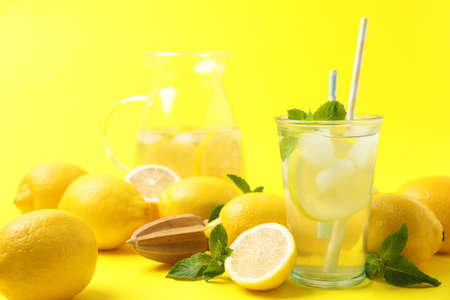 Natural freshly made lemonade with squeezer on yellow background. Summer refreshing drink