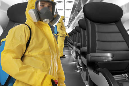 People wearing protective suits cleaning cabin in airplane to prevent spreading of Coronavirus