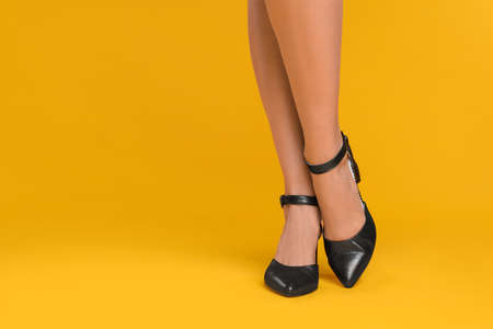 Woman wearing stylish shoes on yellow background, closeup. Space for text