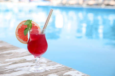 Refreshing cocktail near outdoor swimming pool on sunny day. Space for text