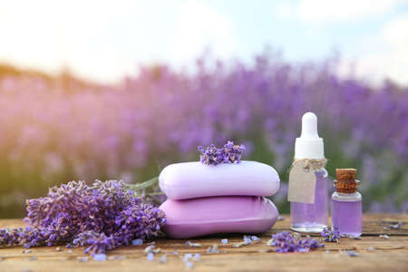 Fresh lavender flowers, soap bars and essential oil on wooden table outdoors, closeup