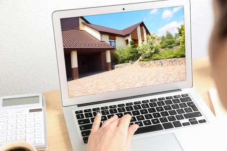 Businesswoman or real estate agent looking through online property portfolio using laptop, closeup