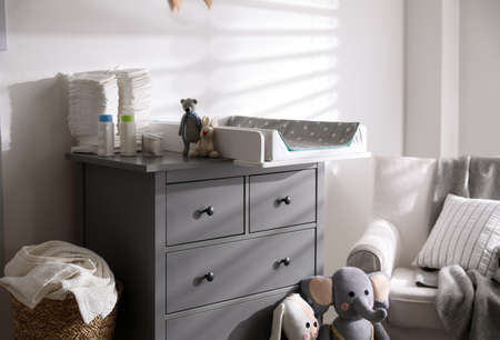 Chest of drawers with changing tray and pad in baby room. Interior design