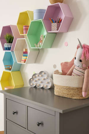 Bright colorful shelves on light wall in room. Interior design