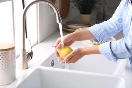 Woman washing fresh ripe pear in kitchen, closeup