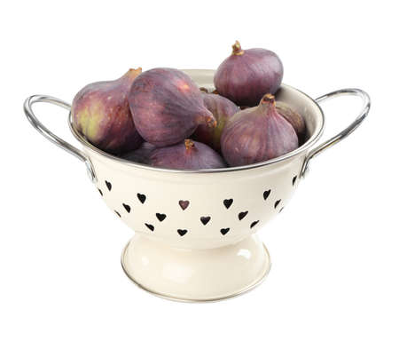 Whole tasty fresh figs in colander on white background
