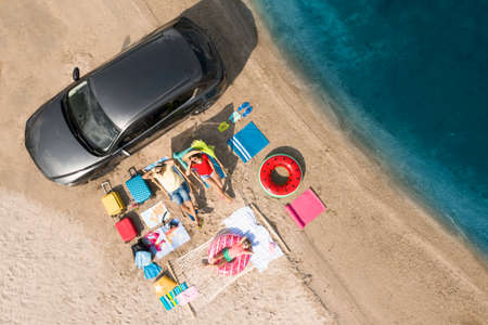 Family with beach accessories and car near river, aerial view. Summer trip