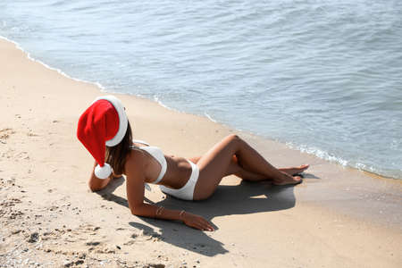 Young woman wearing Santa hat and bikini on beach. Christmas vacation Stock Photo
