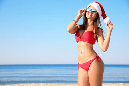 Young woman wearing Santa hat and bikini on beach, space for text. Christmas vacation