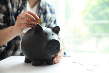 Man putting coin into piggy bank at white table against blurred background, closeup