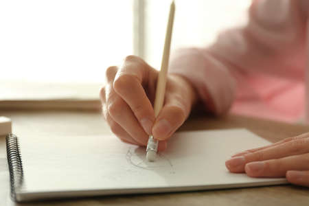 Woman correcting picture in notepad with pencil eraser at wooden table, closeup