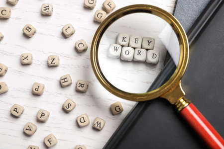 Looking at beads with word KEYWORD through magnifying glass at white wooden table, flat lay
