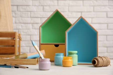 Jars of paints and decorator tools on white table against brick wall. Interior elements