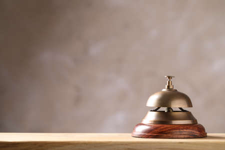 Hotel service bell on wooden table. Space for text