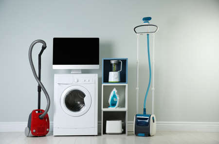 Modern vacuum cleaner and different household appliances near light wall indoors