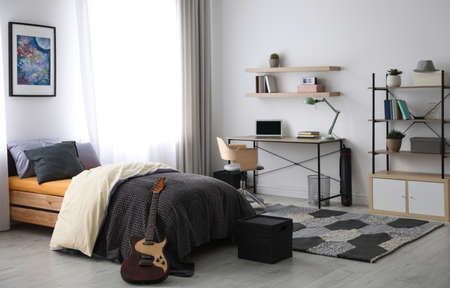 Modern teenager's room interior with workplace and bed Stock Photo