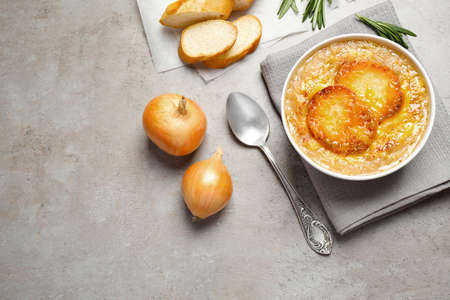 Tasty homemade french onion soup served on gray table, flat lay. Space for text