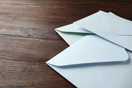 White paper envelopes on wooden table, closeup. Space for text