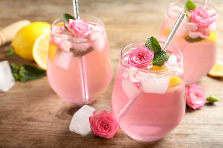 Delicious refreshing drink with rose flowers and lemon slices on wooden table, closeup Stock Photo