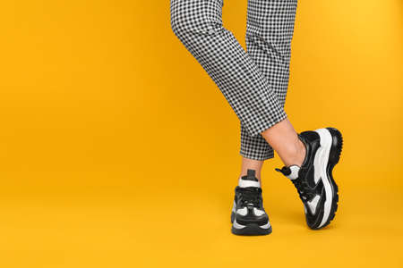 Woman wearing stylish sneakers on yellow background, closeup. Space for text