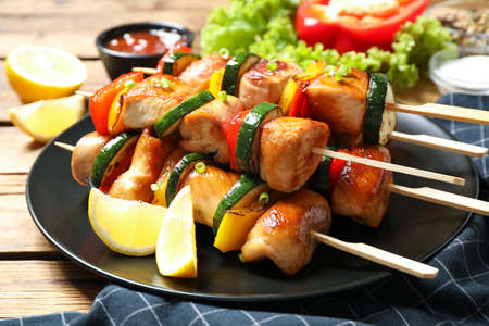 Delicious chicken shish kebabs with vegetables and lemon on wooden table, closeup Stock fotó - 155451991