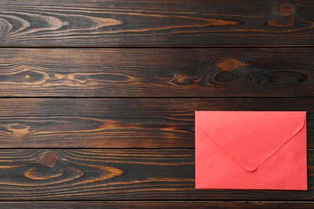Red paper envelope on wooden background, top view. Space for text