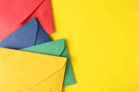 Colorful paper envelopes on yellow background, top view. Space for text Stock Photo