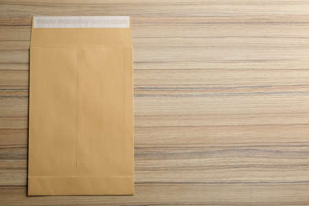 Kraft paper envelope on wooden background, top view. Space for text