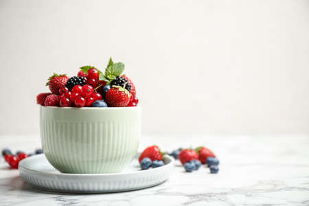 Mix of ripe berries on white marble table. Space for text