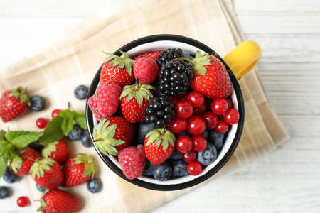 Mix of ripe berries on white wooden table, flat lay