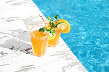 Refreshing cocktail in glasses near outdoor swimming pool on sunny day