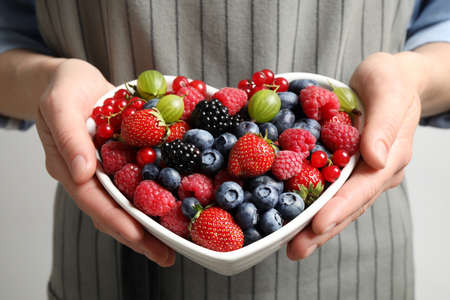 Woman with bowl of delicious summer berries, closeup