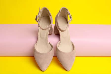 Stylish pink female shoes on yellow background Stock fotó