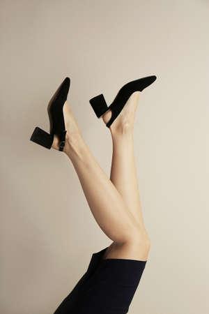 Woman wearing stylish shoes on beige background, closeup