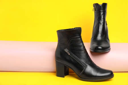Stylish black female boots on yellow background. Space for text