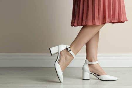 Woman wearing stylish shoes near beige wall indoors, closeup Фото со стока