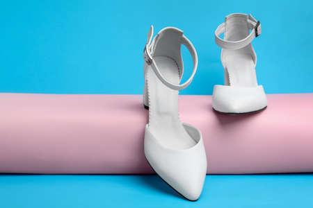 Stylish white female shoes on light blue background