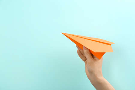 Woman holding paper plane on light blue background, closeup. Space for text
