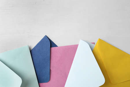 Colorful paper envelopes on white wooden table, flat lay. Space for text