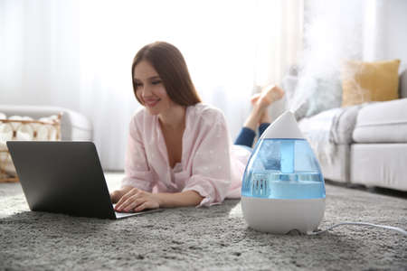 Woman with laptop near modern air humidifier at home Stock fotó