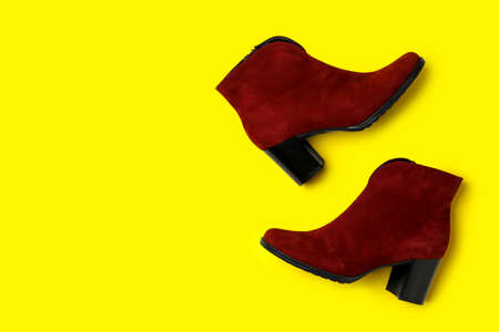 Stylish red female boots on yellow background, flat lay. Space for text