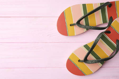 Flip flops and space for text on pink wooden background, top view. Beach objects Stock Photo