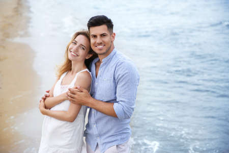 Happy couple on beach, space for text. Romantic walk Stock Photo