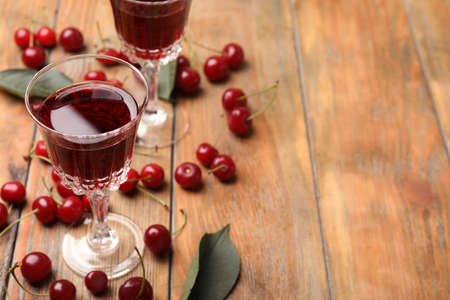 Delicious cherry wine with ripe juicy berries on wooden table. Space for text